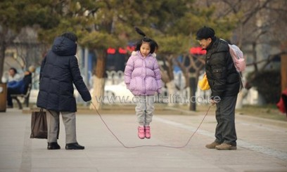 A girl and her parents play with a skipping rope in Beijing/AFP