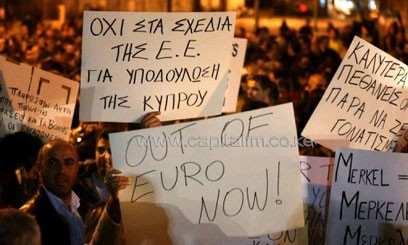 People hold placards during a protest outside parliament in Nicosia on March 21, 2013/AFP