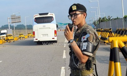 A bus carrying South Korean delegates drive past a soldier at a military checkpoint in Paju on August 14, 2013/AFP