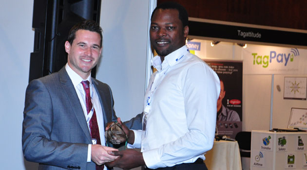 Kennedy Luhombo (R) receives the award from Steve Clarke, Founder of Mobile Money Global during the  6th Mobile Money Global Awards held in Dubai/COURTESY