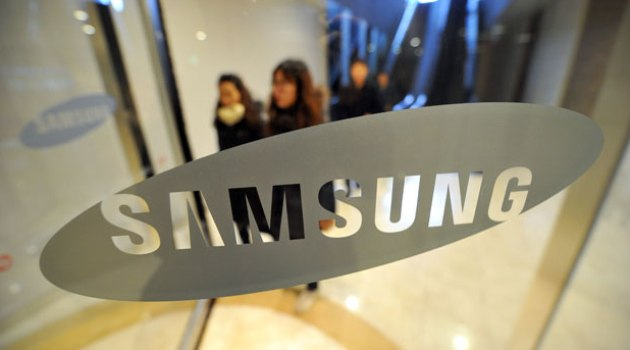 Pedestrians walk past a logo of Samsung Electronics at the company's headquarters in Seoul on January 24, 2014/AFP