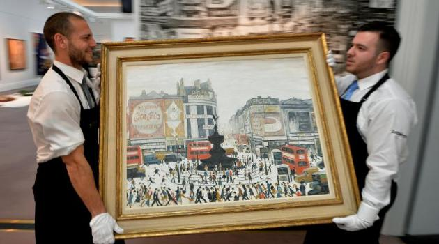 Sotheby's staff hold a work by British artist Laurence Stephen Lowry entitled 'Piccadilly Circus, London' ahead of a sale at Sotheby's auction house in London on March 21, 2014/AFP