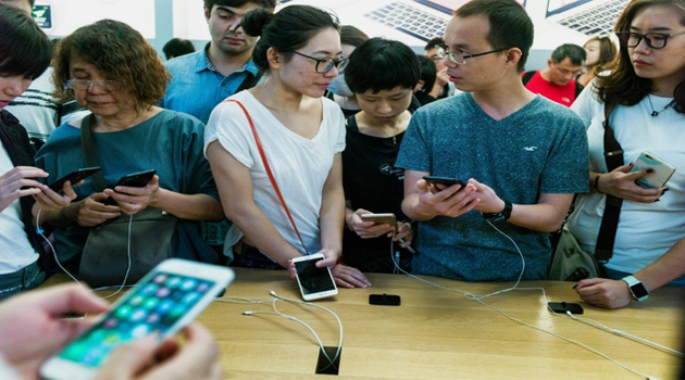 Chinese customers test the new iPhone 7 during the opening sale launch at an Apple store in Beijing on September 16, 2016/AFP