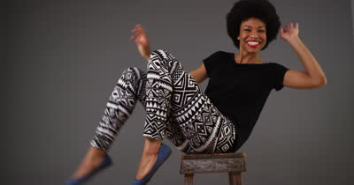 stock-footage-happy-black-woman-dancing-on-chair