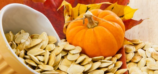 Colorful autumn still life with a yellow bowl overflowing with pumpkin seeds