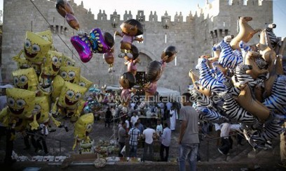 A Palestinian walks past balloons at Damascus Gate on August 8, 2013/AFP