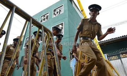 Sri Lankan police stand guard outside a vandalised mosque in Colombo on August 11, 2013/AFP