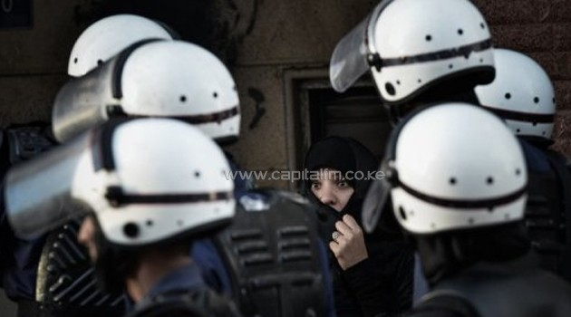 Bahraini police officers walk past a woman in Manama on January 18, 2013/AFP