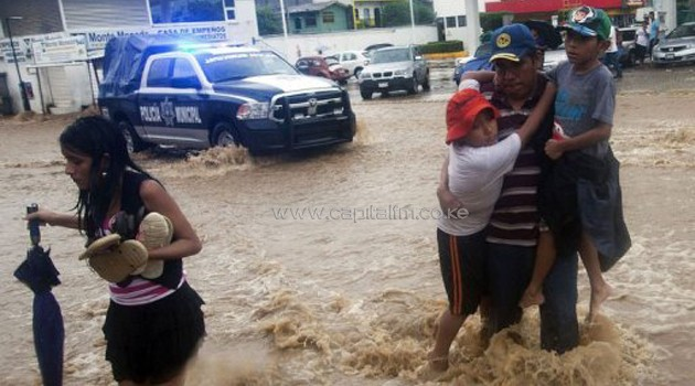 A family wades through a flooded street in Acapulco, Guerrero state, Mexico on September 15, 2013/AFP