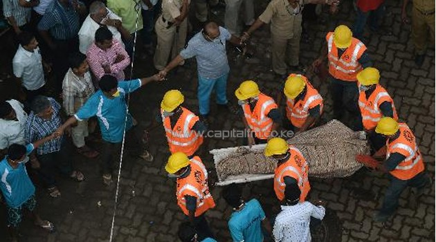 Indian personnel from the National Disaster Relief Force (NDRF) carry a body from the debris of a building collapse site in Mumbai on September 28, 2013/AFP