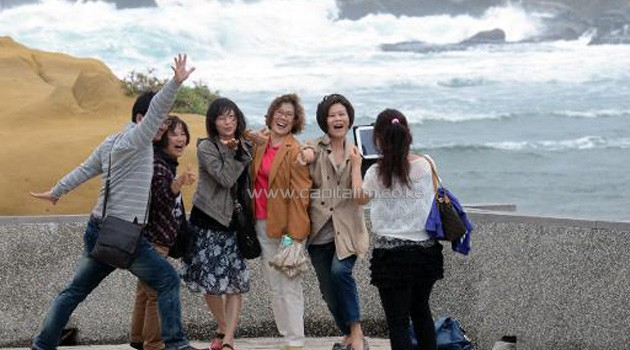 Tourists pose for pictures at Hoping island, in Keelung, northern Taiwan as Typhoon Fitow approaches on October 5, 2013/AFP
