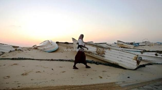 An armed pirate walking past skiffs, used to raid ships on the high-seas, at the coastal town of Hobyo, on November 10, 2009/AFP