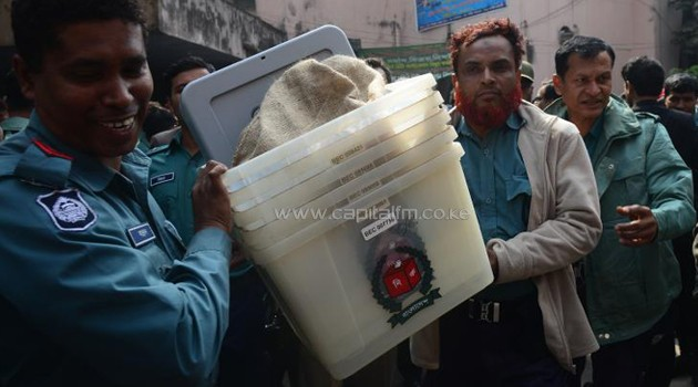 Bangladeshi police officials carry ballot boxes on the eve of general election/AFP