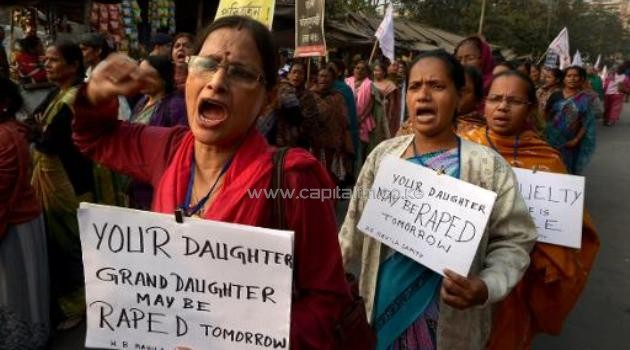Protesters carry posters and shout slogans during a march against the gang-rape and murder of a teenager, in Kolkata on January 3, 2014/AFP