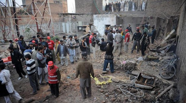 Pakistani security and media personnel gather at the site of a bomb explosion on the outskirts of Peshawar on January 23, 2014/AFP