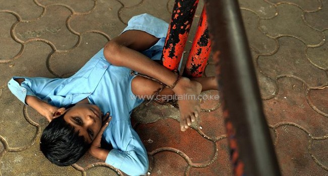 Nine year old Indian boy Lakhan Kale is tied with a cloth rope around his ankle, to a bus-stop pole in Mumbai, May 20, 2014/AFP