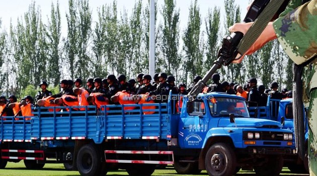 Security forces stand behing the accused (in orange vests) on trucks, during a mass sentencing in Ili prefecture, northwest China's Xinjiang region, on May 27, 2014/AFP