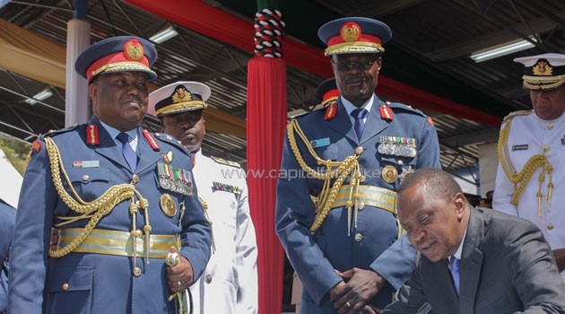 Maj. Gen Joff Otieno (C) standing and other military brass witnessing President Uhuru sign a document/FILE