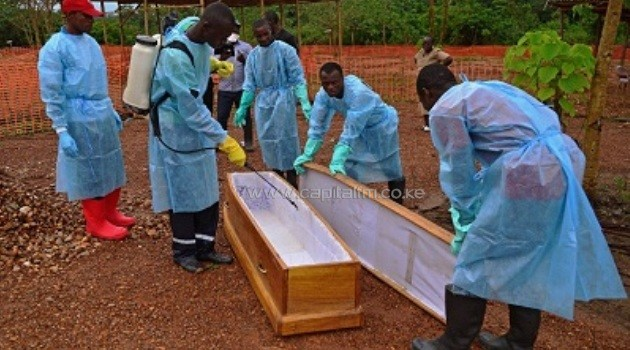 Sierra Leone government burial team members wearing protective clothing disinfect a coffin at the MSF facility in Kailahun, on August 14, 2014/AFP