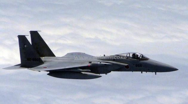A Japanese F-15 jet approaches a Chinese plane (out of frame) in a spot where the two countries' air defence zones overlap, in June 2014/AFP