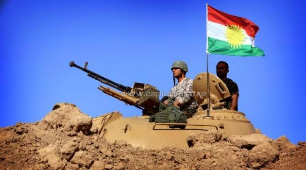 A flag of the autonomous Kurdistan region flies next to Iraqi Kurdish Peshmerga fighters standing on a tank as they hold a position on the front line in Khazer, near the Kurdish checkpoint of Aski kalak, west of Arbil, on September 7, 2014/AFP