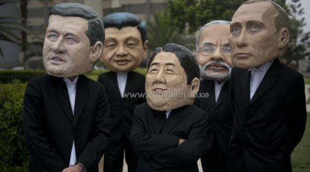 Activist depicting the PM's of Canada, Stephen Harper (L), India, Narendra Modi (2-R) and Japan, Shinzo Abe (C) and presidents of China, Xi Jinping (2-L), and Russia, Vladimir Putin demonstrate at the UN climate talks in Lima, December 12, 2014/AFP