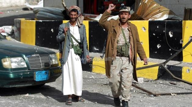Members of the Shiite Huthi movement gesture outside a damaged building near the presidential palace in the Yemeni capital Sanaa on January 20, 2015/AFP