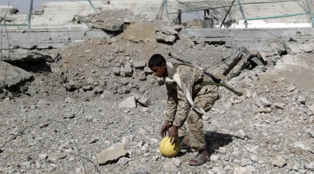 An armed Shiite Huthi rebel picks up a ball on April 12, 2015 at the destroyed compound of Sanaa's al Yarmuk football club/AFP