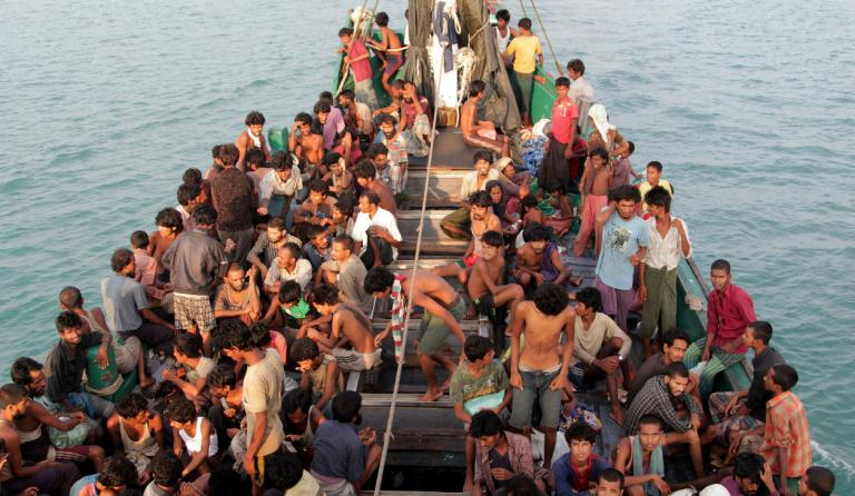 Rohingya migrants sit in a boat off the coast near the city of Geulumpang in Indonesia's East Aceh district of Aceh province before being rescued on May 20, 2015/AFP