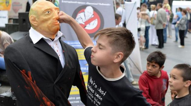 An Ukrainian boy punches a doll representing Russian President Vladimir Putin in a street in Lviv, Ukraine, on May 31, 2015/AFP