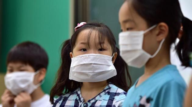 South Korean school students wear face masks during a special class on the MERS virus at an elementary school in Seoul on June 3, 2015/AFP