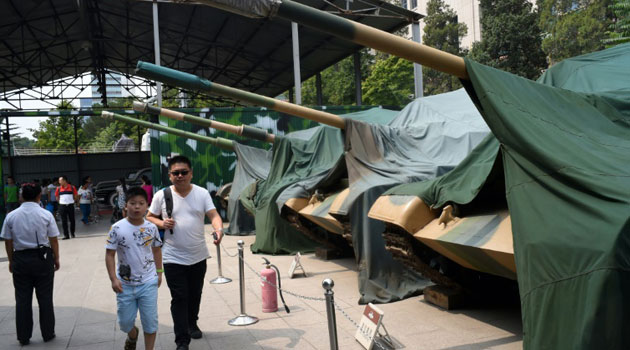 Visitors walk by old army tanks parked outside the Chinese Military museum in Beijing, on August 29, 2015/AFP