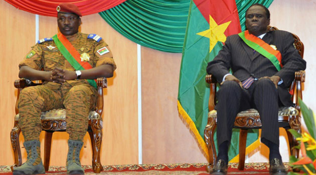 Burkina Faso's Prime Minister Lt. Col. Isaac Zida (L) and interim President Michel Kafando (R) listen during Kafando's inauguration ceremony on November 21, 2014 in Ouagadougou/AFP