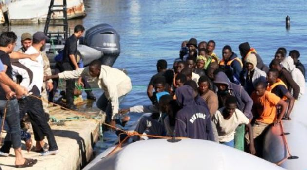 Libyan coastguards tie up a boat carrying rescued migrants at a naval base near Tripoli on September 29, 2015/AFP