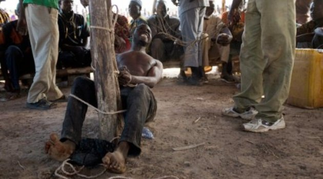 A man suspected of robbery grimaces as he receives lashes from a member of a vigilante group in Kokologo, Burkina Faso/AFP