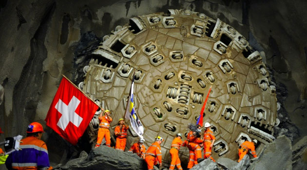 Miners celebrate after a giant drilling machine completes the world's longest tunnel beneath the Swiss Alps/AFP