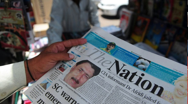 A newspaper bears the photograph of Pakistani surgeon Shakeel Afridi, recruited by the CIA to help find Osama bin Laden, at a newsstand in Karachi on May 24, 2012/FILE