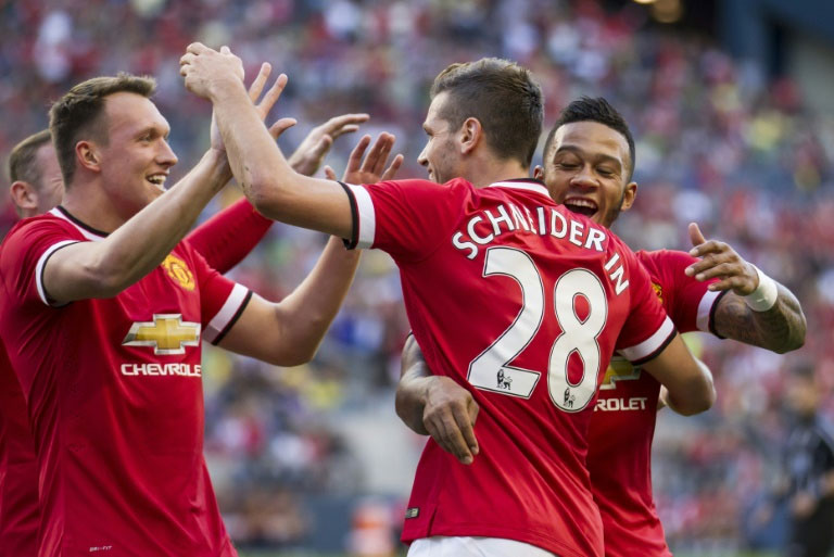 Manchester United's Morgan Schneiderlin (C) is congratulated by teammates Memphis Depay (R) and Phil Jones after he scored against Club America in their International Champions Cup match on July 17,2015 in Seattle, Washington. PHOTO/AFP