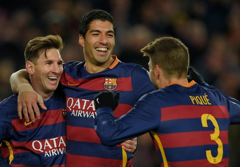 Barcelona forwards Lionel Messi (left) and Luis Suarez (centre) celebrate a goal in their UEFA Champions League match against Roma on November 24, 2015. PHOTO/AFP