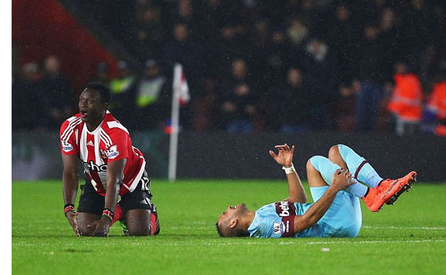 The West Ham midfielder writhes in agony as Wanyama gets up to learn his fate