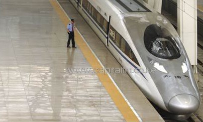 A railway employee stands near two high speed trains at Beijing south railway station/AFP