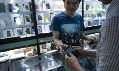 A customer buys a phone at a mobile phone shop in Yangon on June 3, 2013/AFP