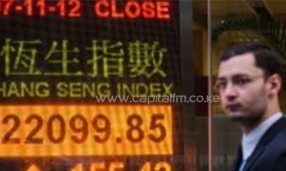 A pedestrian walks past an electronic board displaying the Hang Seng index in Hong Kong /AFP