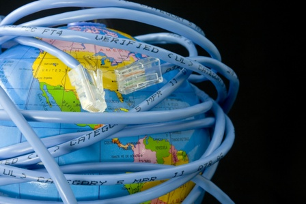 Network cable wrapped around a globe depicting a connected world