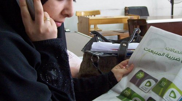 A woman speaks on the phone as she reads an advertisement for Etisalat/AFP