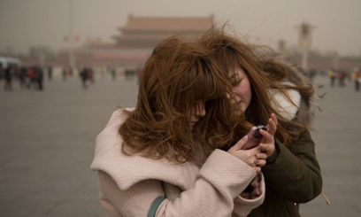 File picture shows two women looking at a mobile phone in Tiananmen Square in Beijing/AFP