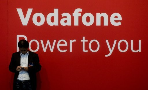 A fair-goer checks his mobile in front of a Vodafone logo at the 53rd IFA electronics trade fair in Berlin on September 10, 2013. Mobile phone operator Vodafone Germany said a hacker had stolen the personal data of two million customers, and that a suspect had been identified.