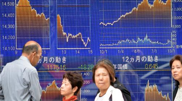 Pedestrians walk past graphs of the Nikkei key index of the Tokyo Stock Exchange in Tokyo on October 2, 2013/AFP