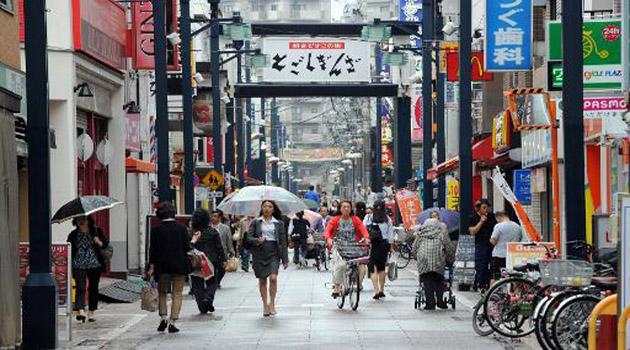 Pedestrians walk through the Togoshi shopping district in Tokyo on October 1, 2013/AFP