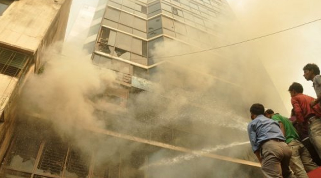 Onlookers watch as firefighters try to control a garment factory fire in Bangladesh, on November 26, 2012/AFP